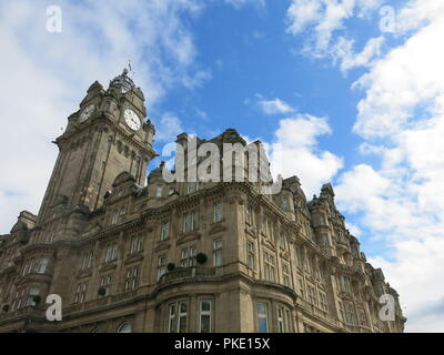 The clocktower and landmark building of the Balmoral Hotel dominates the skyline of Edinburgh's Princes Street at the Waverley Station end - Stock Photo