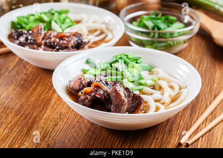 Japanese Udon noodles with beef, green onion and soup in a dish - Stock Photo