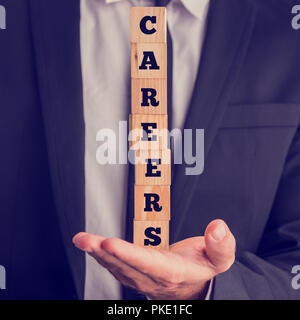 Close Up of Businessman Holding Vertical Stack of Letter Blocks Spelling Careers in Palm of Hand. - Stock Photo