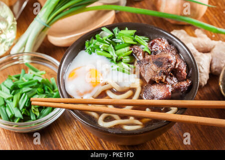 Japanese Udon noodles with beef, egg, green onion and soup in a brown bowl - Stock Photo