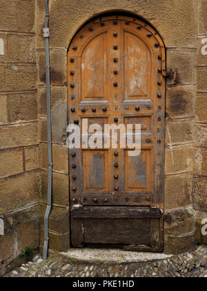 repairs needed to arched studded wooden side door to church in Seix in the Ariege Pyrennees, France - Stock Photo