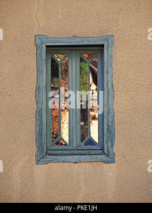 distorted reflections of sunlit buildings opposite shining in blue-framed panelled window of cracked building in the Ariege Pyrennees, France - Stock Photo