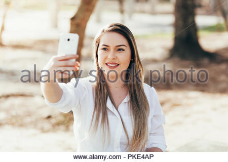 Technology, communication and people concept - happy woman taking selfie with smartphone and sitting on bench in summer park - Stock Photo