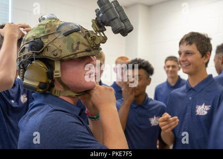 Morrisville, N.C.- Team members of the U.S.A. Baseball 14 and Under National Team Development Program (NTDP) try on and learn about the gear used by NC National Guard Soldiers during a visit to the 449th Theater Aviation Brigade's Headquarters in Morrisville, North Carolina on July 26, 2018. The Athletes, which play their third and final game of the series on Friday July 27th, also learned about teamwork and selfless sacrifice from NCNG leaders. - Stock Photo