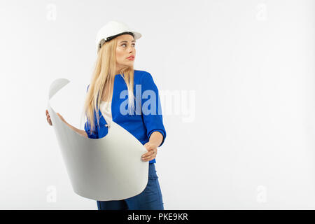 Employee woman in suit standing in helmet with paper documents on white background. architect considers drawings - Stock Photo