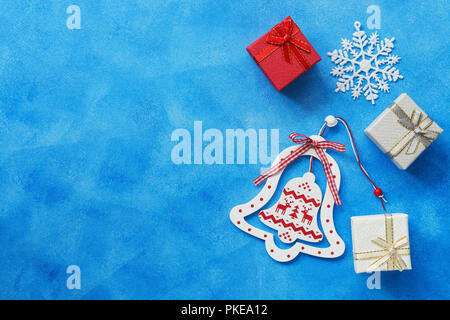 Christmas background. Christmas wooden bell, gifts box, snowflake on a blue background. Top view, copy space - Stock Photo