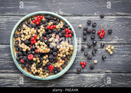 A variety of currant berries yellow and red,black and red raspberries, on a rustic ceramic dish, wooden old table. The view from the top. - Stock Photo