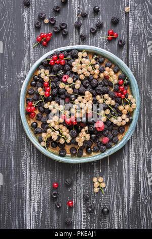 Fresh berries-raspberries,black raspberries, currants on a ceramic dish, rustic wooden dark background. - Stock Photo