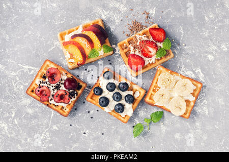 Belgian waffles with berries and fruit on a grey background. The view from the top,flat lay - Stock Photo