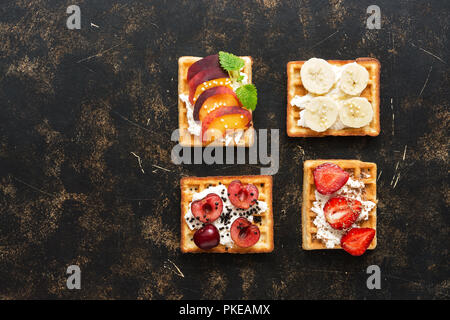 Traditional Belgian waffles with fruits and berries, top view. Dark background, copy space. Wafers with strawberries, cherries, peaches and bananas - Stock Photo