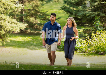 A mixed race married couple walking in a city park and holding hands as they enjoy time together on a warm sunny afternoon; Edmonton, Alberta, Canada - Stock Photo