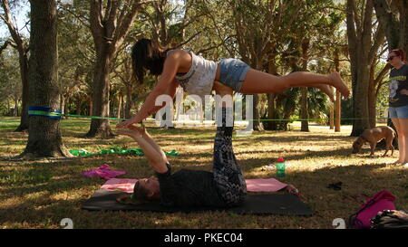 Young women doing practicing acro yoga on a public park in Florida, JUPITER, FLORIDA. USA - JUNE 17, 2017. - Stock Photo