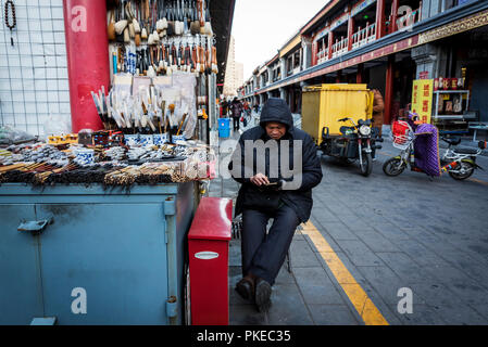 A vendor selling calligraphy sets at the Panjiayuan Antique Market; Beijing, China - Stock Photo