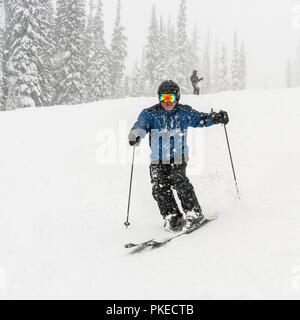 Skier going downhill in a heavy snowfall at Sun Peaks Resort; Kamloops, British Columbia, Canada - Stock Photo