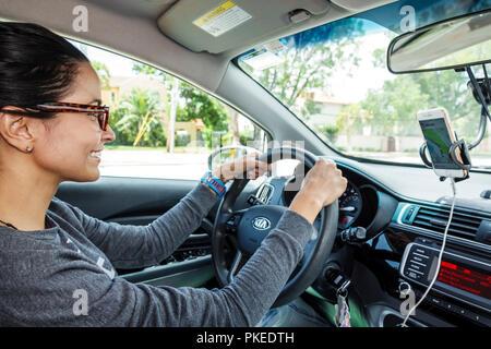 Miami Beach Florida Uber Driver Working Driving Hispanic Woman KIA Car Steering Wheel Dashboard Smartphone GPS