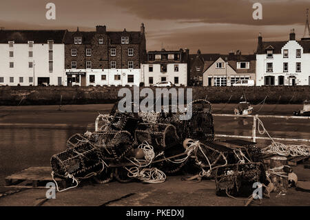 A view of Stonehaven harbour in Scotland from the harbour wall, with lobster pots in the foreground. All at low tide - Stock Photo
