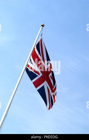 Flagpole with Union Jack Flag blowing in the wind - Stock Photo