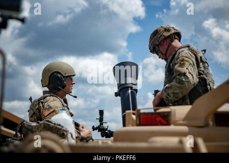 Gunner Pfc. Austin Hutchenson (left) and Assistant Gunner Pfc.Terry Tompakou (right) of B Co., 6th Squadron, 8th Cavalry Regiment, 2nd Armored Brigade Combat Team prepare to receive gun data from their Tank Commander at Gunnery IV, V, and VI at Fort Stewart, Ga., July 23. The mortar platoon's mission is to provide close and immediate indirect fire support for battalions and companies. - Stock Photo