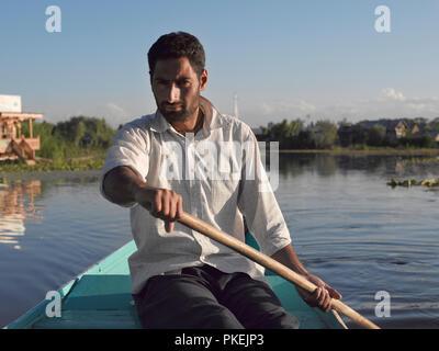 A Kashimiri man rows a boat used for tourist rides on Dal Lake, SRINAGAR, KASHMIR, INDIA, ASIA - Stock Photo