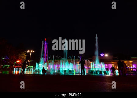 Bright colorful fountains at night on the embankment of the Amur river in the city of Khabarovsk. Bright color. Illumination of lanterns. - Stock Photo