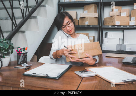 woman counting on package on a shelf - Stock Photo
