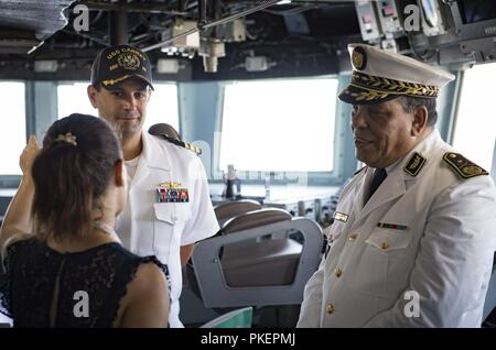 Algeria (July 29, 2018) Cmdr. Tyson Young, center, commanding officer of the Arleigh Burke-class guided-missile destroyer USS Carney (DDG 64), provides a tour of the ship to Algerian Gen. Sameh Zine-Eddine, commander of Central Maritime Zone, 1st Military Region, during the ship's visit to Algiers, Algeria, July 29, 2018. Carney, forward-deployed to Rota, Spain, is on its fifth patrol in the U.S. 6th Fleet area of operations in support of regional allies and partners as well as U.S. national security interests in Europe and Africa. - Stock Photo