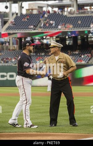 Major Gen. John R. Ewers Jr., staff judge advocate to the Commandant of the Marine Corps, shakes the hand of Washington Nationals catcher, Spencer Kieboom, during U.S. Marine Corps Day at Nationals Park, Washington D.C., July 31, 2018. The Washington Nationals hosted Marines stationed around the National Capital Region to participate in pre-game events to honor the Marine Corps. - Stock Photo