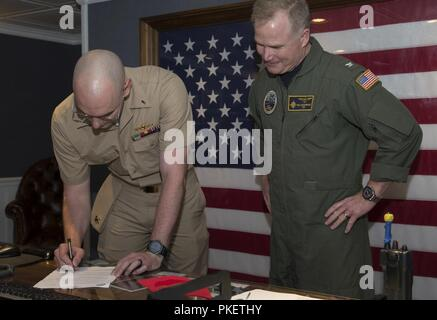 NEWPORT NEWS, Va. (Aug. 1, 2018) Lt. j.g. Zachary Klassen, from Phoenix, assigned to USS Gerald R. Ford's (CVN 78) weapons department, signs his delivery of permanent appointment paperwork during a promotion ceremony aboard Ford. - Stock Photo