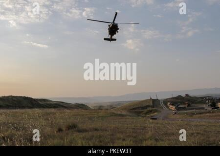 An HH-60 Black Hawk helicopter approaches a landing zone during Noble Partner 18 during a medical evacuation exercise at the Vaziani Training Area, Georgia.  The exercise validated the joint medical evacuation procedures of U.S. and Georgia Armed Forces. - Stock Photo