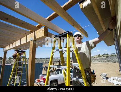 U.S. Air Force Staff Sgt. David Berning, 133rd Civil Engineer Squadron Structures shop, snaps a chalk line across multiple boards for an overhang on a modular home in Gallup, N.M., July 26, 2018. The homes are being constructed for Navajo Veterans as part of joint Innovative Readiness Training program led by the Naval Mobile Construction Battalion 22 in partnership with the Southwest Indian Foundation. - Stock Photo