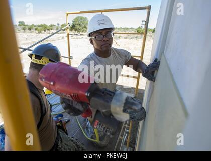 U.S. Air Force Staff Sgt. Robert Johnson, an electrician from the 133rd Civil Engineer Squadron, nails siding onto a modular home in Gallup, N.M., July 26, 2018. The homes are being constructed for Navajo Veterans as part of joint Innovative Readiness Training program led by the Naval Mobile Construction Battalion 22 in partnership with the Southwest Indian Foundation. - Stock Photo