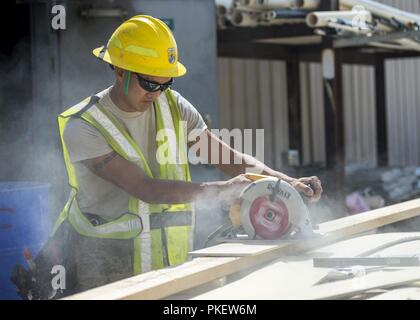 U.S. Air Force Staff Sgt. Mark Spitznogle, 133rd Civil Engineer Squadron Structures shop, saws though a board while framing up a new transportable modular home in Gallup, N.M., July 26, 2018. The homes are being constructed for Navajo Veterans as part of joint Innovative Readiness Training program led by the Naval Mobile Construction Battalion 22 in partnership with the Southwest Indian Foundation. - Stock Photo