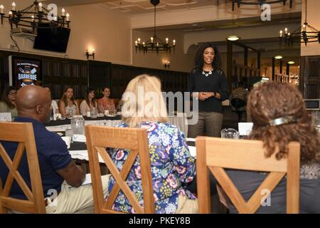 Tonya Wright, spouse of Chief Master Sgt. of the Air Force Kaleth O. Wright, speaks with Team Mildenhall spouses during a breakfast at the Gateway Dining Facility at RAF Mildenhall, England, Aug. 2, 2018. Mrs. Wright met with Team Mildenhall spouses, where she answered questions and listened to their perspectives as military spouses. - Stock Photo