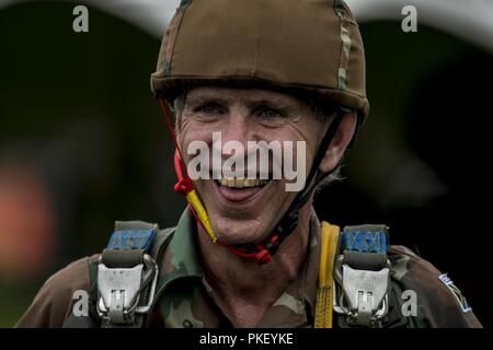 A South African Paratrooper smiles during Leapfest 2018 at the University of Rhode Island in West Kingston, R.I., Aug. 1, 2018. Leapfest is the largest, longest-standing, international static line parachute training event and competition hosted by the 56th Troop Command, Rhode Island Army National Guard, to promote high level technical training and esprit de corps within the International Airborne community. Over 300 Paratroopers from nine different countries are participating this year. - Stock Photo