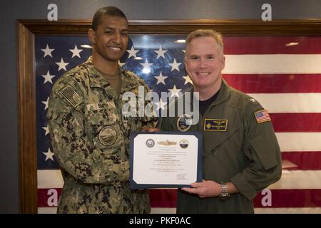 NEWPORT NEWS, Va. (Aug. 3, 2018) Lt. Terrence Smith, from Virginia Beach, Virginia, assigned to USS Gerald R. Ford's (CVN 78) supply department, receives his Surface Warfare Supply Corps Officer certificate from Capt. Richard McCormack, Ford's commanding officer. - Stock Photo