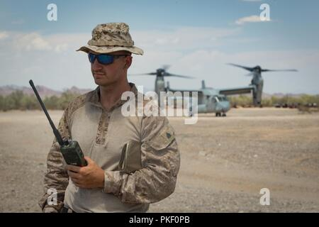 U.S. Marine Corps Sgt. Kaleb Coy, a fire support Marine with Headquarters Battery, 11th Marine Regiment, 1st Marine Division (MARDIV), completes joint terminal attack controller missions during exercise Summer Fury, at Range 2057 South, Calif., Aug. 2, 2018. The exercise was conducted to increase 1st MARDIV operations proficiency by incorporating establishing, transitioning and phasing control of aircraft and missiles across multiple locations. - Stock Photo