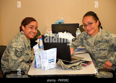 ALPENA, Mich. — Mother and daughter, Master Sgt. Sheila Lipp, a command support staff member of the 127th Maintenance Group, and Tech Sgt. Chanel Daniels, a food service lead of the 127th Force Support Squadron, both units of the Selfridge Air National Guard Base, Mich., work on finalizing their orders after performing an operational readiness assessment at the Alpena Combat Readiness Training Center on Aug. 2, 2018. More than 500 Citizen-Airmen of the 127th Wing mobilized in a simulated deployment that created opportunities to practice their job proficiency while being assessed for wartime ta - Stock Photo