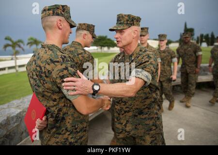 Sgt. Alexander J. Kraska and Sgt. Andrew M. Rief are congratulated by peers and seniors following their promotion ceremony at  Camp Courtney, Okinawa, Japan, Aug. 2, 2018. The Marines and Sailor were meritoriously promoted to the next rank by the III Marine Expeditionary Force commanding general and sergeant major. - Stock Photo