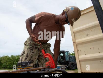 Utilitiesman 2nd Class Rashaad McKenzie, from St. Petersburg, Florida, assigned to Naval Mobile Construction Battalion (NMCB) 11, Det. Guam cuts a copper pipe during the construction of a restroom and shower facility at Polaris Point, Naval Base Guam, August 7, 2018. NMCB-11 provides expeditionary construction and engineering capabilities that includes maintenance and operation of expeditionary bases and facilities, tactical sustainment bridging, humanitarian assistance through construction civic action details and civic action teams and theater disaster response capabilities in the U.S. 7th F - Stock Photo