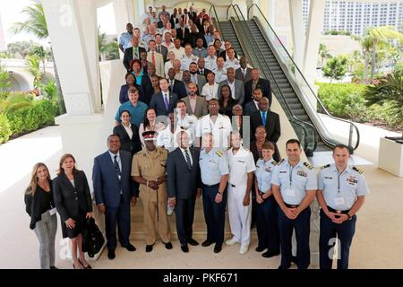 Multiple members from the Coast Guard Office of Maritime Law Enforcement, Royal Bahamas Police Force and the Royal Bahamas Defence Force take a moment for a group photo during the 6th Multilateral Maritime Interdiction and Prosecution Summit held Nassau, Bahamas Tuesday, Aug. 7, 2018. More than 87 maritime counter drug professionals from operational and legal communities in attendance during the 6th MMIPS representing 15 countries across the Central and Eastern Caribbean. U.S. Coast Guard photo of Coast Guard Office of Maritime Law Enforcement - Stock Photo