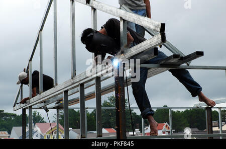 Asian man welder climb on steel frame and welding to build