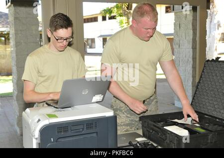 U.S. Air Force Staff Sgt. Christopher Chase and Senior Airman Derrick Langlais, cyber systems operators assigned to the 158th Fighter Wing, Vermont Air National Guard, establish communications at the community center in Molokai, Hawaii for Tropic Care for Maui County 2018 Aug. 11, 2018. Tropic Care Maui County 2018 is a joint-service Innovative Readiness Training mission led by the Air National Guard and supported by members of the Air Force, Army, Navy Reserve, and Marine Corps Reserve. Health clinics at Central Maui, Kihei, Lahaina, Hana, Molokai, and Lanai will run from August 11-19, provid - Stock Photo