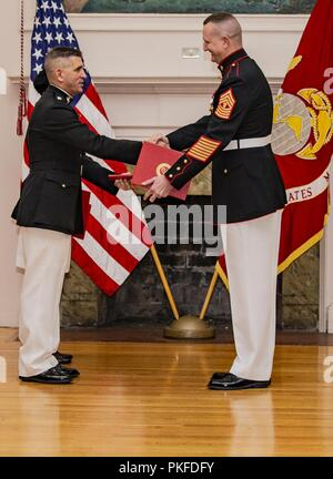 Retired U.S. Marine Corps Lt. Col. Matthew Howes, left, presents an award to Master Gunnery Sgt. Bryan Boyd, senior enlisted advisor, Installations and Logistics, Harry Lee Hall, Marine Corps Base Quantico, Va, July 26, 2018. Boyd retired after 30 years of faithful service. - Stock Photo
