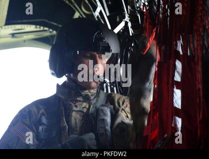 U.S. Army Sgt. Nathan Eberhardt, crew chief, 2nd General Support Aviation Battalion, 135th Aviation Regiment, Colorado Army National Guard, uses his internal microphone to speak to the flight crew of his CH-47 Chinook helicopter during exercise Northern Strike 18 in Alpena Mich., Aug. 9, 2018.  Riding along on the Chinook were officers from the Royal Jordanian Air Force who worked alongside their Colorado Army National Guard aviation counterparts to share air-ground integration best practices and strengthen their relationship. - Stock Photo