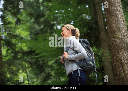 A Happy Woman hiking in a forest - Stock Photo