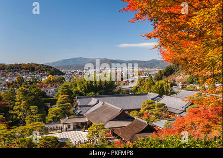 Autumn colour in Kyoto, Japan. A view over Ginkaku-ji zen temple, also known as the Silver Pavilion, with the city and mountains in the background - Stock Photo