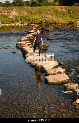 UK, Yorkshire, Wharfedale, Grassington, woman using stepping stones across River Wharfe during dry summer weather - Stock Photo