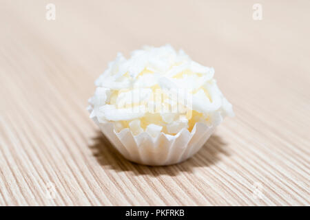 Beijinho is a handmade candy from Brazil. Made with condensed milk and coconut. Children brithday party sweet. Overhead of candy ball in white backgro - Stock Photo