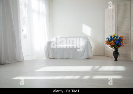 home decor white room with sofa and flowers in a vase - Stock Photo