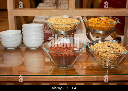 Variety of healthy dietary fiber cereals in glass bowls ready for breakfast - oat flakes, corn flakes - Stock Photo